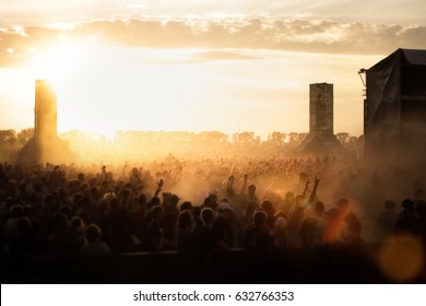 Open air view from the stage. Silhouettes of the summer festival. The lights of a sun.