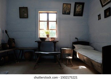 Open Air Village Museum Lublin 'Muzeum Wsi Lubelskiej', Poland, 09/04/2019 interior of a typical Polish cottage from 19th century with simple bed, table, benches, religious artwork and small window