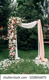 Open air wedding ceremony with wedding arch decorated with flowers and white fabric