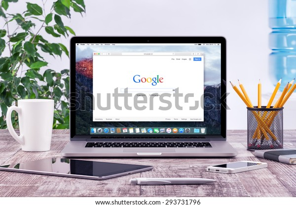 Open Apple 15 inch MacBook Pro Retina with an open tab in Safari which shows Google search web page with ipad and iphone on the wooden office desk workplace. Varna, Bulgaria - May 29, 2015.