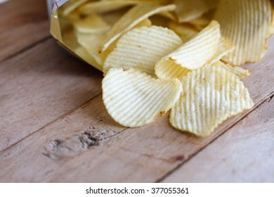 Open bag with potato chips on wood table