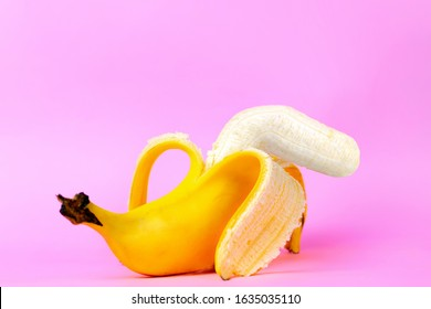 An open banana symbolizing the male sexual organ in an UN-erect state or impotence. Pink background. Concept of potency and men's health and power. Copy soace