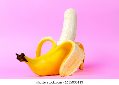An open banana symbolizing the male sexual organ in an erect state. Pink background. Concept of potency and men's health and strength. Copy space