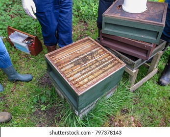 Open beehive with a pile of supers and a feeder next to it.