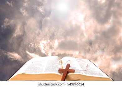 Open bible against the clouds with a wooden cross over it and bright light in the background