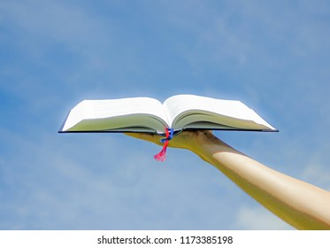 Open bible with blue sky background