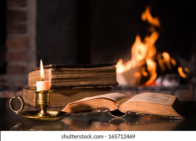 An open Bible book with a burning candle in front of fireplace