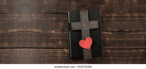 Open Bible. Bible book on a wooden table. Wooden cross of Jesus. Red heart. The concept of love for God's Word.