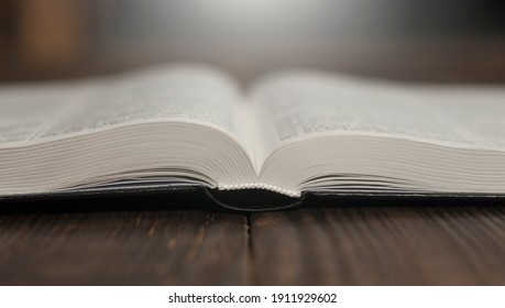 Open Bible book on a wooden table.