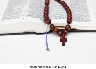 open bible book and rosary on white background