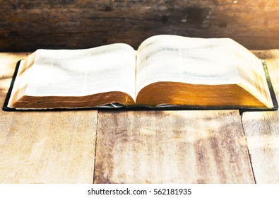 open bible with burred page on wooden background with copy space