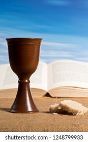 Open bible with chalice of wine and bread