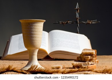 Open bible with chalice of wine and cross