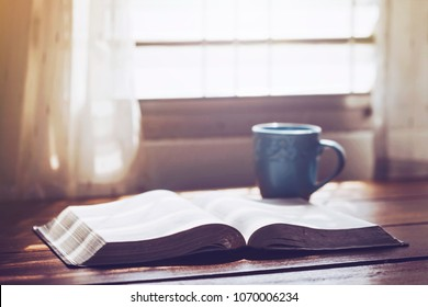 open bible with a coffee cup on wooden table near window, morning devotion concept