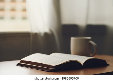 Open bible with a cup of coffee for morning devotion on wooden table with window light.book and coffee cup on wooden table.