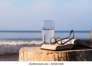 Open Bible and a glass of water on the coast