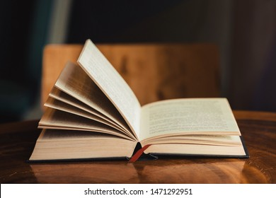 Open bible for morning devotion on wooden table with window light