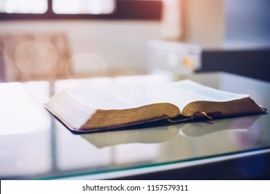 Open bible on office desk with window light reflected, Christian background with copy space.