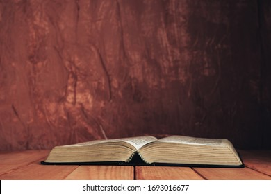 Open bible on a red old wooden table. Beautiful brown wall background.