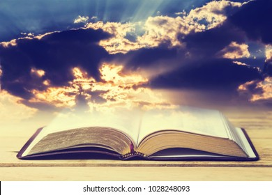 open bible on wooden table over the light through dark cloudy sunset sky. Christian concept show the word of God is the light of mandkind