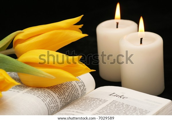 Open bible, tulips and candles