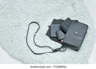 Open black bag with dropped things, notebook, mobile phone and purse. Fur on background. Fashion concept