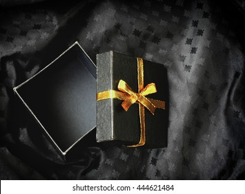 open black gift box with golden ribbon bow on silk textured fabric