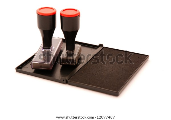 An open black ink pad with two stamps isolated on white background