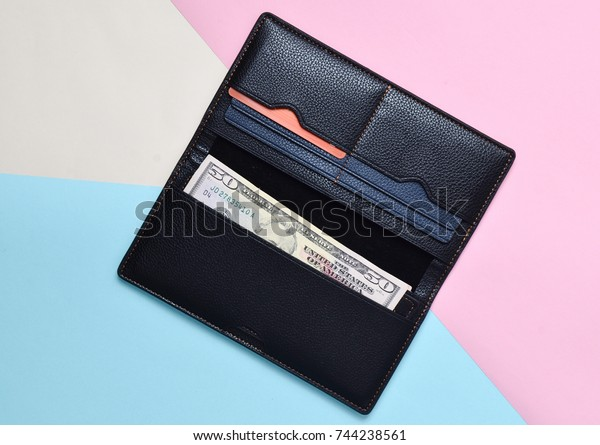 An open black purse with dolar bills and credit cards on a multicolored pastel background. Trend of minimalism. Top view.
