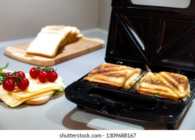 Open black sandwich toaster in kitchen with ingredients