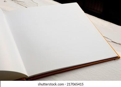 Open blank brochure on a wooden table