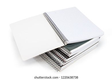 Open blank exercise book with pages of squared paper and wire spiral binding on stack of other exercise books on a white background