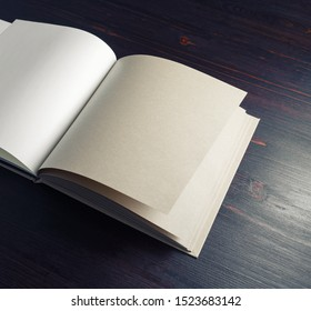 Open blank kraft paper book or sketchbook on wood table background. Branding mock up. Copy space for text.