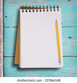 Open blank notebook on grunge wood background in green color with yellow pencil.