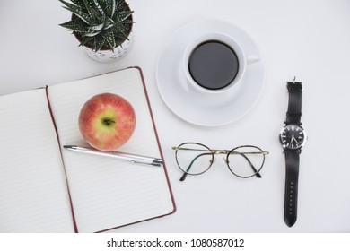Open blank notebook with a pen, fresh red apple, espresso coffee, wristwatch and potted succulent plant on a white background viewed from the top down