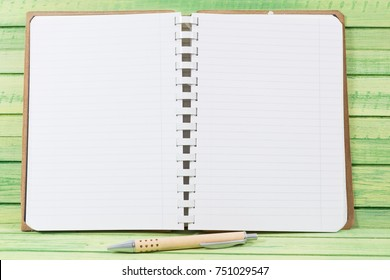 Open blank notebook with pen on wooden board as diary or journal concept