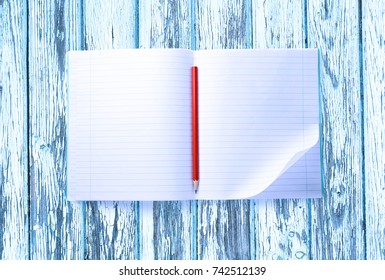 Open blank notebook with red pencil closeup