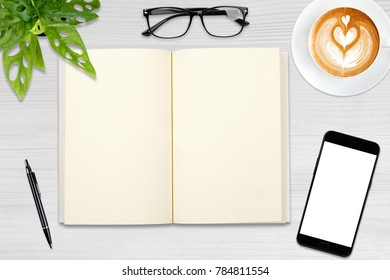 An open blank notebook, smartphone with pen and a cup of latte coffee on wooden table.