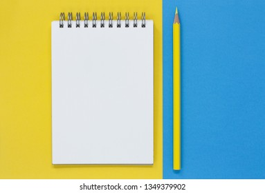 Open blank notepad with a yellow pencil, on a blue and yellow flat lay background