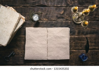 Open blank page book, old literature, pocket watch and a inkwell with quill pen on a writer wooden table background.