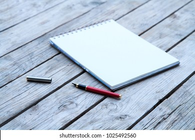 Open Blank Page notebook and pen on a rustic wooden desk.