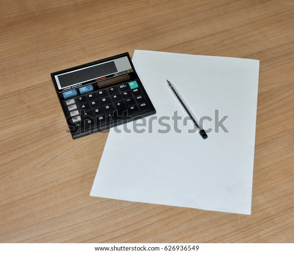 Open blank page with pen and calculator on wooden background picture.
