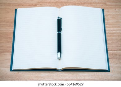 Open blank paper leather notebook with pen on wooden table