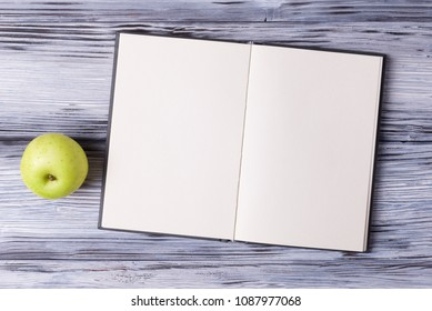 Open blank sketchbook and green apple over white wooden background.
