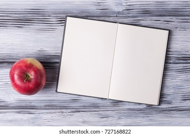 Open blank sketchbook and red apple over white wooden background