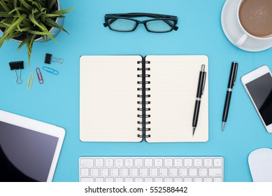 Open blank spiral notebook with office supplies, notebook, pen, pencil, tablet, phone, flower, eye glasses and coffee cup on blue desk table, Top view with copy space