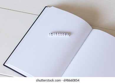 Open blank white notebook on the wooden desk with word with cubes - introvert