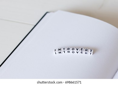 Open blank white notebook on the wooden desk with word with cubes - introvert. Closed-up