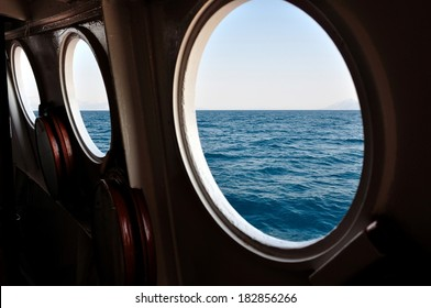 Open boat porthole with ocean view close up