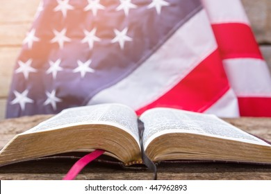 Open book and american flag. Open book on wooden surface. Value your independence. Freedom for every man.